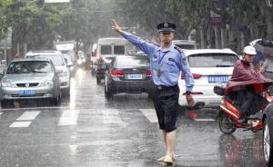 17日上午,上海杨浦平凉路内江路口,一位民警在雨中指挥交通。6月17日凌晨2时,上海中心气象台发布橙色暴雨预警信号,强降水对早高峰出行较大造成影响。范筱明 图