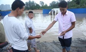 2015年6月25日,河南郑州,郑州祈福大道王庄村口被淹,村民在水里捞车牌卖钱。一位车主没能在水中找到自己的车牌,只能无奈地将钱递给村民。