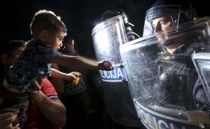 当地时间2015年9月18日,克罗地亚斯洛文尼亚边境,一名难民的孩子和斯洛文尼亚警察默默玩耍。