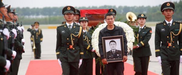 礼兵肩抬灵柩,申亮亮的哥哥申明明手捧遗像,一步一步走向灵车。