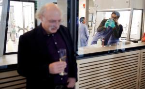 """当地时间10月4日,诺贝尔物理学奖评委会在斯德哥尔摩的瑞典皇家科学院宣布,2016年诺贝尔物理学奖物理学奖授予三位美国科学家:戴维·索利斯、邓肯·霍尔丹和迈克尔·科斯特利茨,以表彰他们在理论上发现了物质的拓扑相变和拓扑相。图为一名工作人员正在用手机""""偷拍""""邓肯·霍尔丹。"""