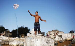 当地时间2016年7月20日报道,巴西里约北部贫民窟的一处墓地内,男孩在里头玩风筝。墓园里有20多个孩子都在等待风可以把风筝吹起来。里约奥运将于8月5日召开,但对这些生活在贫民窟里的孩子来说,缺少运动和娱乐的空间。