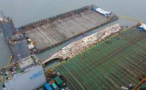 """当地时间2017年3月23日,韩国全罗南道珍岛郡沉船海域,""""世越""""号被捞起抬高,最终将被半潜船转运至港口。"""