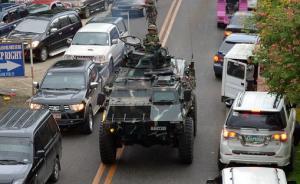 """从5月23日下午开始,菲政府军及警察在马拉维市与""""穆特组织""""武装分子及""""阿布沙耶夫""""极端组织头目哈皮隆率领的武装分子持续交火。图为当地时间5月25日,马拉维民众纷纷逃离家园避难,政府军的装甲车和逃难民众的车辆混杂在一起。视觉中国 图"""