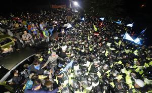 当地时间2017年9月7日,韩国星州,距离驻韩美军萨德系统部署地点星州高尔夫球场最近的韶成里村口,大批民众集结,封锁道路,抵抗即将于7日凌晨部署的萨德系统剩余四台发射车。韩国警方出动大量警力,试图冲破民众封锁道路,现场爆发大规模冲突,目前伤亡情况不明。视觉中国 图