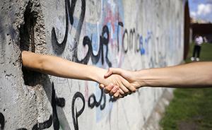早安,全世界都在看↑柏林墙建立56周年,游客穿越墙洞握手